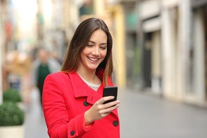 Girl walking and texting on the smart phone in the street in red.jpg