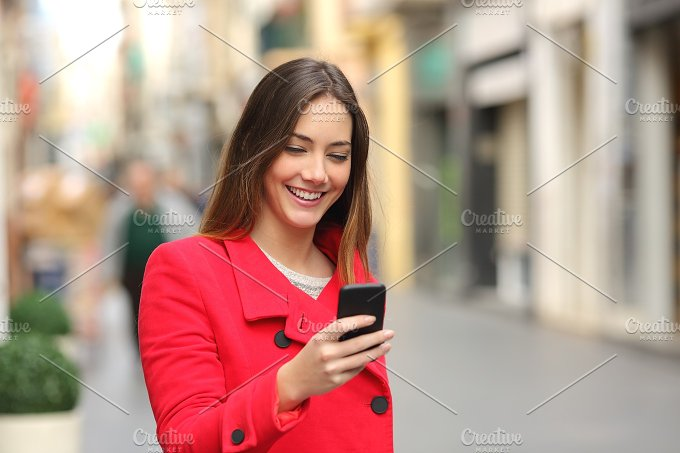 Girl walking and texting on the smart phone in the street in red.jpg - Technology