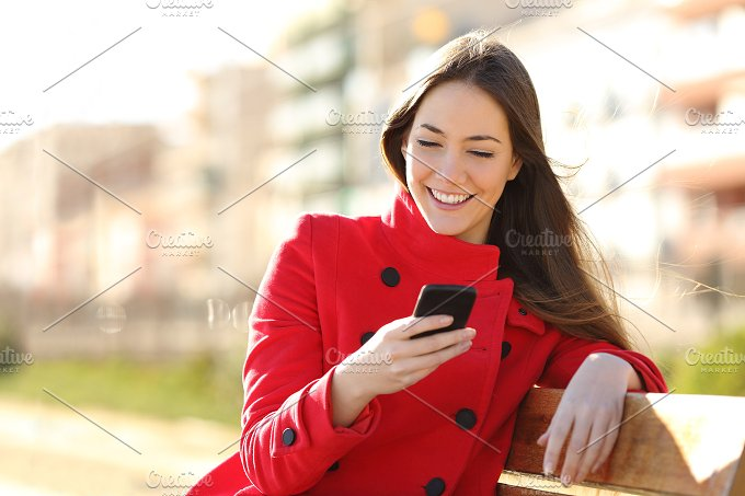 Girl texting on the smart phone sitting in a park.jpg - Technology