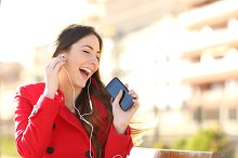 Funny girl listening to the music with earphones from a phone.jpg