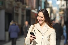 Girl walking and texting on the smart phone in the street in winter.jpg