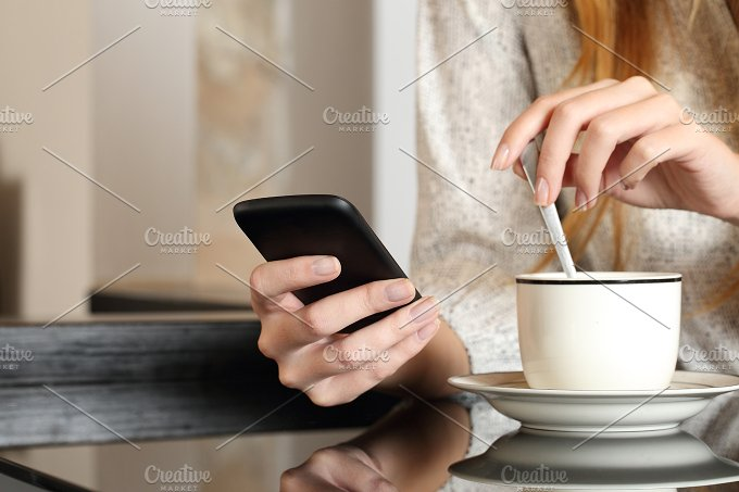 Hand using a smart phone during breakfast at home.jpg - Technology