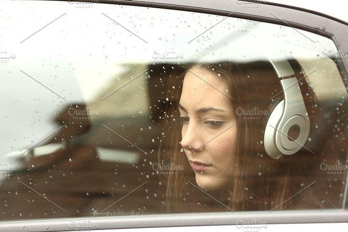 Sad teenager girl in a car with headphones.jpg - Transportation