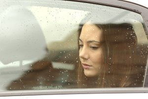 Sad woman looking down through a car window.jpg