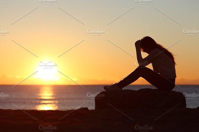 Sad woman silhouette worried on the beach.jpg - People