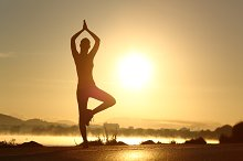 Silhouette of a fitness woman exercising yoga meditation exercise.jpg