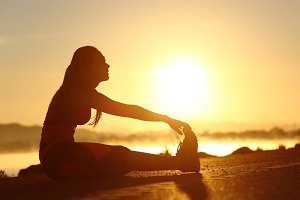Silhouette of a fitness woman stretching at sunset.jpg
