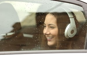 Teenager with headphones listening to the music in a car.jpg