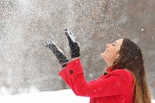 Woman in red throwing snow in the air in winter.jpg