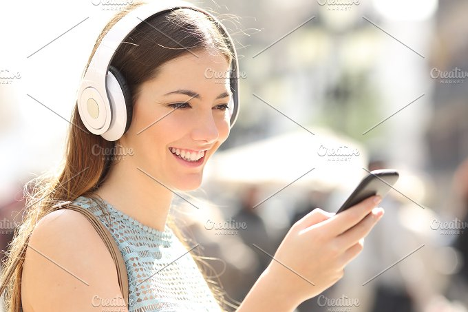 Woman listening music from a smart phone in the street.jpg - Technology