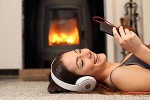 Woman listening to the music from a smartphone at home.jpg