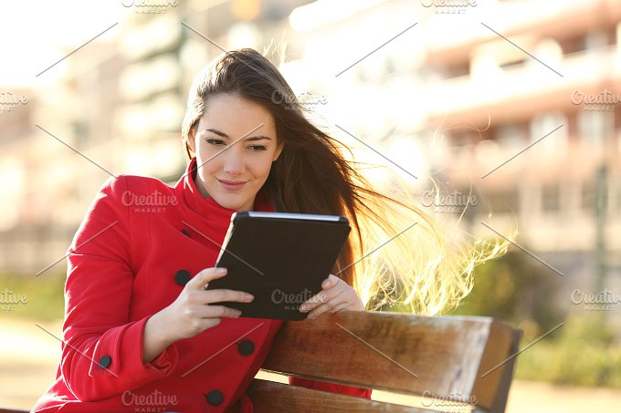 Woman reading a ebook or tablet in an urban park.jpg - Technology
