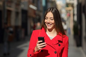 Woman using a smart phone while walk in the street.jpg