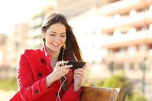 Woman watching videos in a smart phone with earphones.jpg