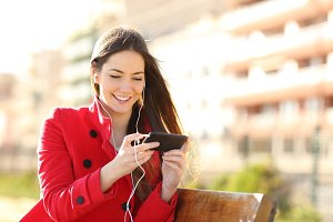 Woman watching videos in a smart phone with earphones.jpg