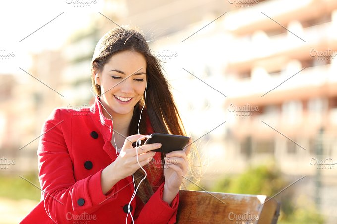 Woman watching videos in a smart phone with earphones.jpg - Technology