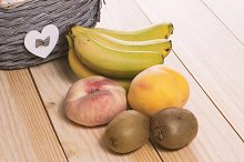 Fruits with basket on wooden table