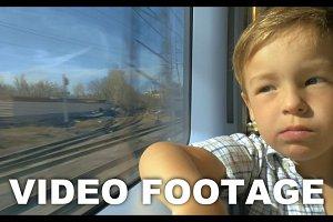 Little boy looking out train window