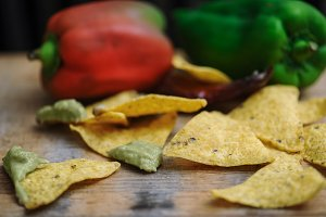 homemade guacamole with corn chips top view on wooden table