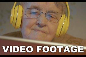 Senior woman headphones using tablet