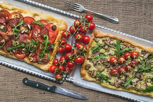 Pizzas with fresh arugula & tomatoes