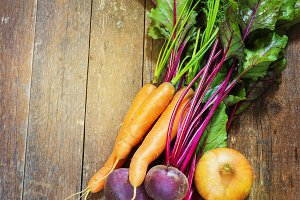 Different, fresh, young vegetables, beets, carrots, onions  lie on a wooden table. rustic style.