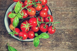 Fresh cherry tomatoes in a metal bowl on a dark background