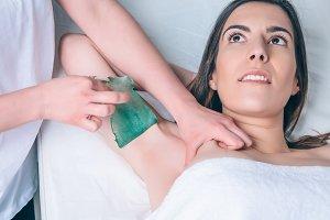 Closeup of woman armpit depilation