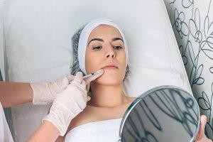 Woman looks lips treatment in mirror