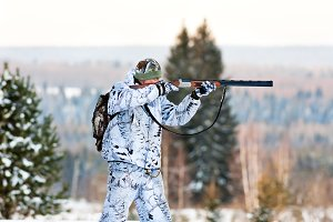 hunter shooting from a gun in winter