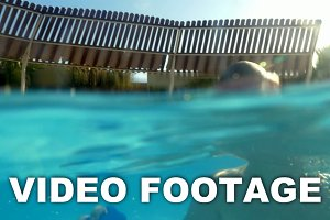 Child enjoying swimming outdoor pool