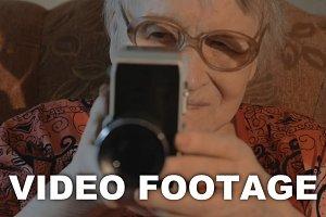 Senior woman filming with retro