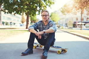 Young man sitting on skateboard