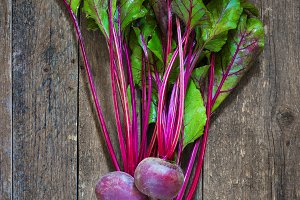 Bunch of Baby Beets with foliage, on wooden background