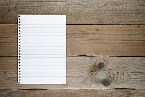 Lined paper on wooden background