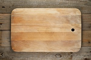 Chopping board on wooden background