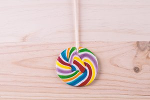 Multicolored lollipop on wood
