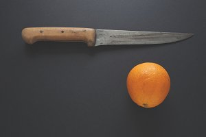 Old kitchen knife and orange