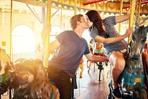 romantic couple kissing carousel