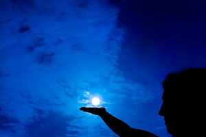 Woman holding full moon in hand