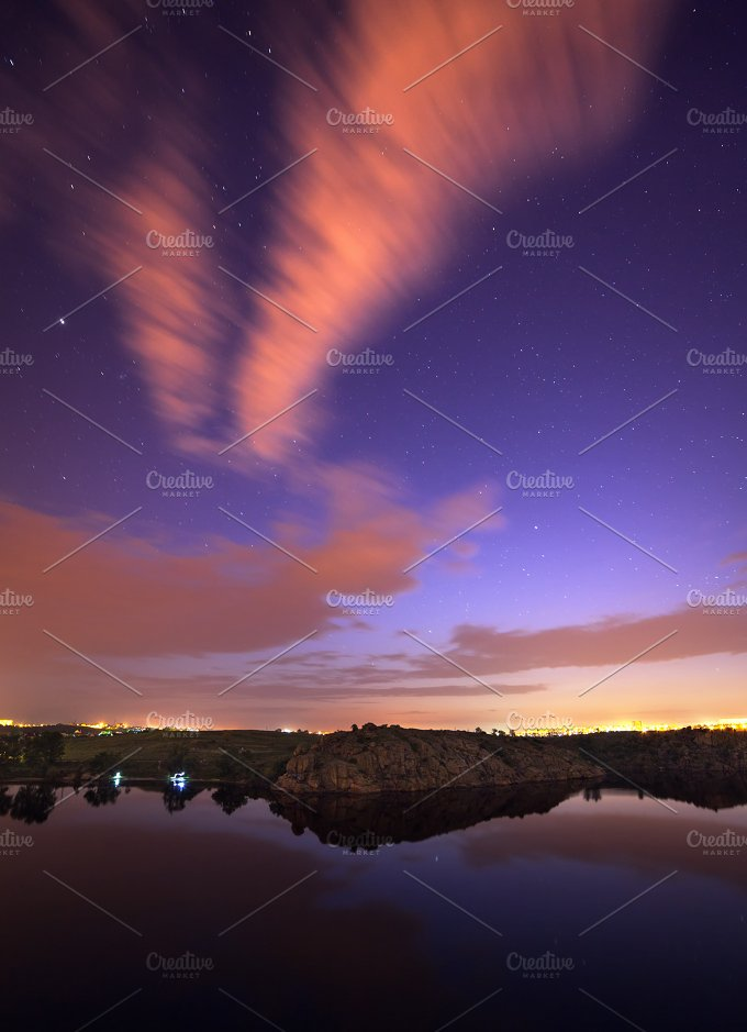 Beautiful night sky at the river with stars, clouds and reflections in the water. Summer in Ukraine - Nature