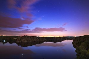 Beautiful night sky at the river with stars, clouds and reflections in the water. Summer in Ukraine