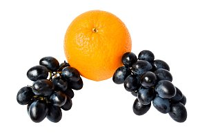 Bunches of black grapes and orange