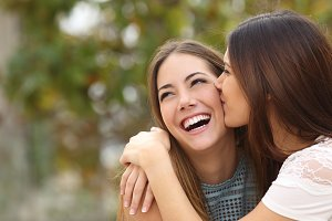 Two funny women friends laughing and kissing.jpg