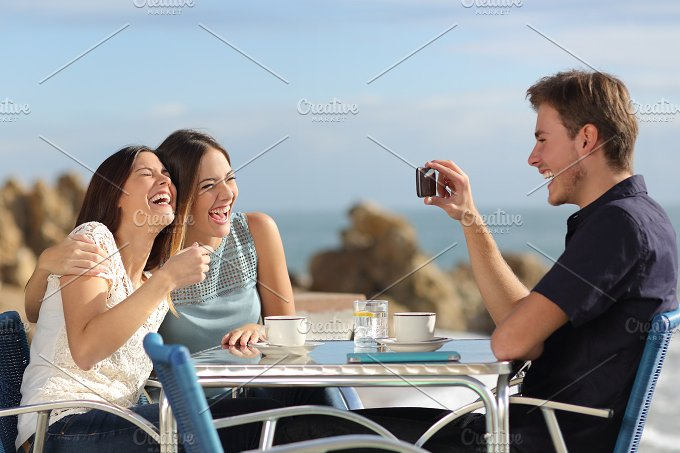 Friends laughing and taking photos with a smart phone.jpg - Technology