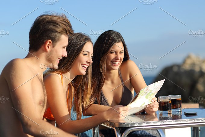 Friends on vacations consulting a guide in an hotel terrace.jpg - Holidays