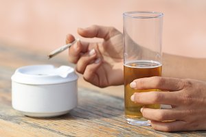 Hands holding a cigarette smoking and drinking alcohol.jpg