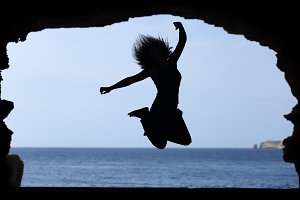 Silhouette of a woman jumping on the beach.jpg