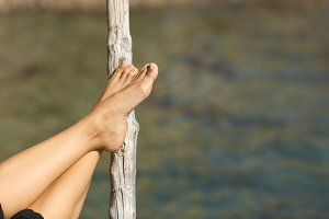 Woman feet relaxing on holidays in a beach or lake.jpg
