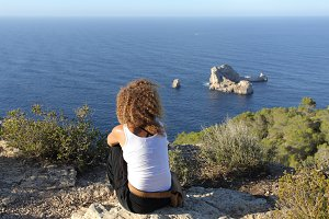 Woman pensive relaxing on a cliff in Ibiza island.jpg